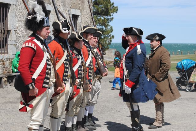 `Enemies Conversing` -- Old Fort Niagara's British Redcoats meet face-to-face with an officer of the Continental Army, portrayed by event organizer Tommy Thompson of Hoisington's New York Rangers, and an American militiaman, portrayed by Tony Consiglio, also of Hoisington's, during Patriots Day Weekend. (Photo by Charlotte Clark)